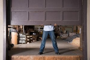man lifting garage door to his small business considering a business broker to sell his business